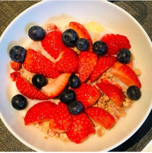 over-filtered photo of granola with strawberries and blueberries.